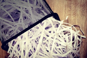 Strips of destroyed paper from shredder in trash can on wooden background